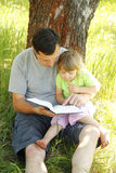 Young father with his little daughter reads the Bible Stock Photography