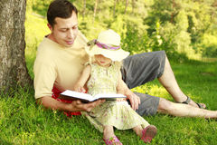 Young father with his little daughter reads the Bible Royalty Free Stock Images