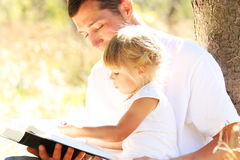 Young father with his little daughter reads the Bible Stock Images