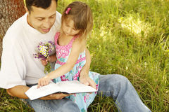 Young father with his little daughter reads the Bible Royalty Free Stock Photos