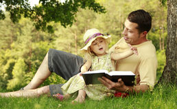 Young father with his little daughter reads the Bible Stock Photos
