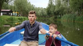 Young father and his little son float together in boat among green trees. Happy family having fun at the weekend in park on lake. Little son talking to his stock video footage