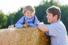 Young father and his little son having fun on yellow hay field i Stock Photos