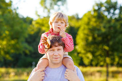 Young father and his little son having fun on yellow hay field i Royalty Free Stock Images