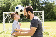 Young father with his little son playing football on football pitch. A Young father with his little son playing football on football pitch Royalty Free Stock Photo
