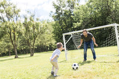 Young father with his little son playing football on football pitch Royalty Free Stock Image