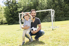 Young father with his little son playing football on football pitch. A Young father with his little son playing football on football pitch Stock Photos