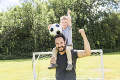 Young father with his little son playing football on football pitch stock image