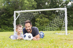 Young father with his little son playing football on football pitch royalty free stock photography