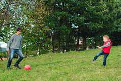 Young father with his little son playing football on green grassy lawn. Young father with his little son playing football on a green grassy lawn Stock Photo