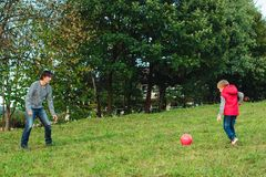 Young father with his little son playing football on green grassy lawn. Young father with his little son playing football on a green grassy lawn royalty free stock photography