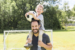 Young father with his little son playing football on football pitch. A Young father with his little son playing football on football pitch Royalty Free Stock Image