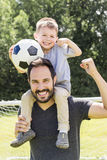 Young father with his little son playing football on football pitch royalty free stock photos