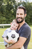 Young father with his little son playing football on football pitch stock photography