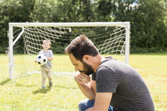 Young father with his little son playing football on football pitch stock photos