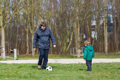 Young father with his little son playing football on playground. Royalty Free Stock Images