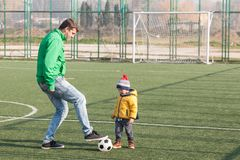 Young father with his little son playing football, soccer in the park royalty free stock images