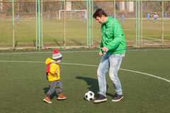 Young father with his little son playing football, soccer in the park Stock Images