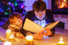 Young father and his little son reading book by a fireplace on C Stock Photography