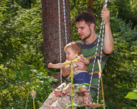 Young father and his little son on the swing. On green background Stock Image