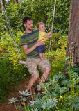Young father and his little son swinging. Sunny day. August Stock Images