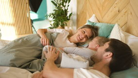 Young father and his little son wake up their mother and family play in bed at home stock video
