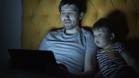 Young father and his little son watching cartoon movie using laptop computer while lying in bed in evening at home. Before sleeping stock footage