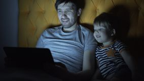 Young father and his little son watching cartoon movie using laptop computer while lying in bed in evening at home Stock Photography