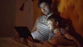 Young father and his little son watching cartoon movie using tablet computer while lying in bed in evening at home stock photos