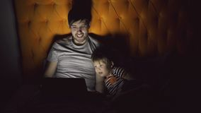 Young father and his little son watching cartoon movie using tablet computer and talking while lying in bed in evening. At home before sleeping stock video