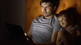 Young father and his little son watching cartoon movie using tablet computer and talking while lying in bed in evening royalty free stock image