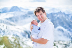Young father and his newborn baby in mountains Stock Images