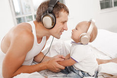Young father with his nine months old som on the bed at home Stock Image
