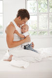 Young father with his nine months old son on the bed at home Royalty Free Stock Photography