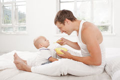 Young father with his nine months old son on the bed at home Stock Photos