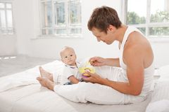 Young father with his nine months old son on the bed at home Stock Photo
