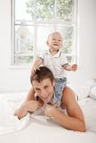 Young father with his nine months old son on the bed at home. Young smiling father with his nine months old son on the bed at home on white home background. son royalty free stock photos