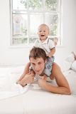 Young father with his nine months old son on the. Young smiling father with his nine months old son on the bed at home on white home background. son sitting on royalty free stock photos
