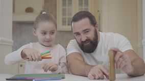 Young father and his small cute daughter are sitting in living room and watching an experiment with markers and throw. Father and his small cute daughter are stock video footage