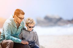 Father and son together. Young father and his smiling son enjoying time together at the beach, father`s day concept, copy space on the right Stock Images