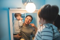 Young father with his son brushing teeth. And looking happy stock photo