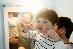 Young father with his son brushing teeth. And looking happy Stock Photography