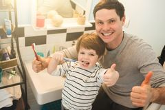 Young father with his son brushing teeth. And looking happy royalty free stock photos