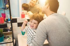 Young father with his son brushing teeth. And looking happy stock images