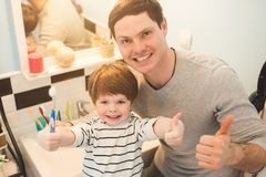 Young father with his son brushing teeth. And looking happy royalty free stock images