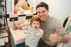 Young father with his son brushing teeth. And looking happy stock image