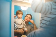Young father with his son brushing teeth. And looking happy royalty free stock image