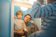 Young father with his son brushing teeth. And looking happy Royalty Free Stock Photography