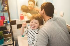 Young father with his son brushing teeth. And looking happy Royalty Free Stock Photo