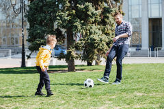 Young father and his son playing football in a park Royalty Free Stock Photos